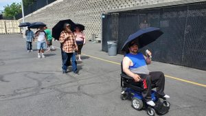People are given umbrellas to help with the heat as they wait outside the arena.